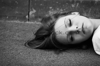 Portrait of sleeping young girl lying on asphalt. Black and whit