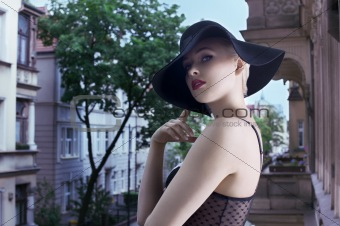 young blond fashion woman in elegant black hat  in urban backgro