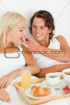 Portrait of handsome man giving a strawberry to his girlfriend