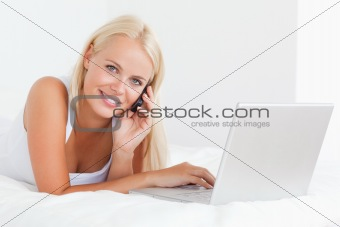 Blonde woman on the phone with a notebook