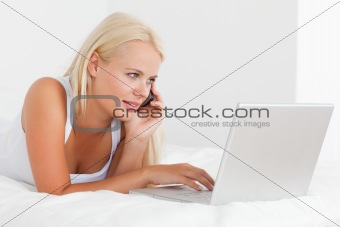 Blonde woman on the phone using a notebook