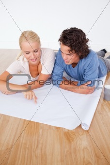 Portrait of a woman showing a point on a plan to her boyfriend
