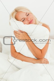 Blonde woman holding a pillow