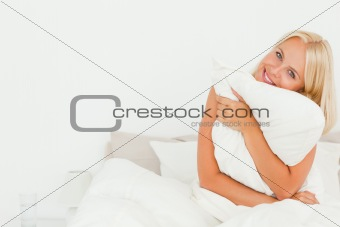 Cute woman holding a pillow