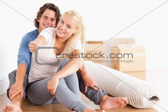 Cute woman sitting with her boyfriend giving keys