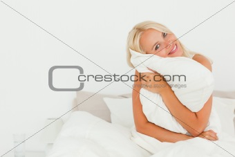 Lovely woman holding a pillow