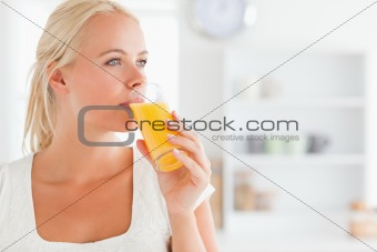 Close up of a blonde woman drinking juice