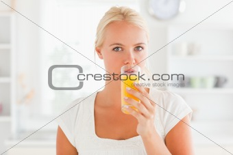 Blonde woman drinking juice
