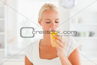 Blonde woman drinking orange juice