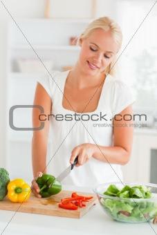 Blonde woman slicing pepper