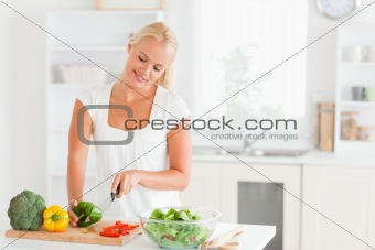 Beautiful woman slicing pepper