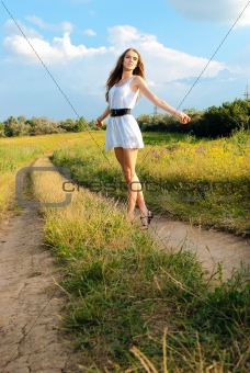 young happy girl walking in meadow