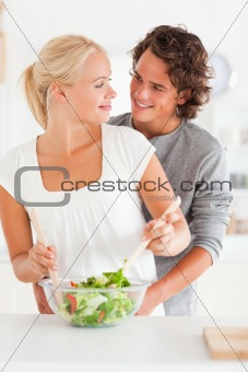 Portrait of a smiling couple preparing a salad