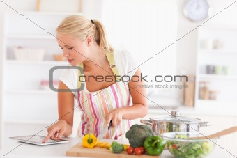 Blonde woman using a tablet computer to cook