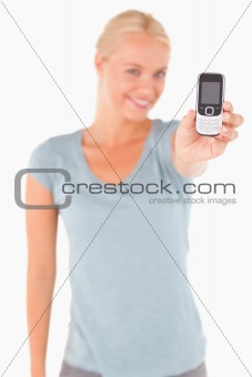 Smiling blond woman showing a phone