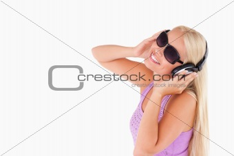 Charming woman with earphones and sunglasses