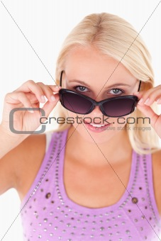Charming lady peeking over her sunglasses