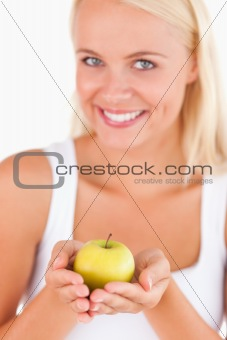 Charming blond woman holding an apple