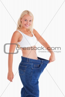 Cute woman wearing to big jeans