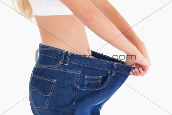 Woman wearing to big jeans