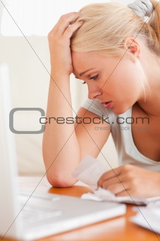Close up of a Worried blond woman accounting