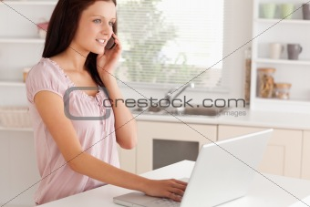A woman telephoning next to laptop