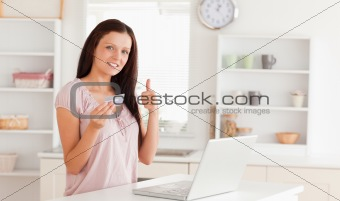 Woman with credit card and thumb up
