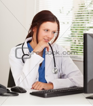 Female doctor looking to pc screen