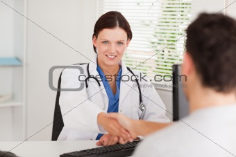 Female doctor hand shaking with patient