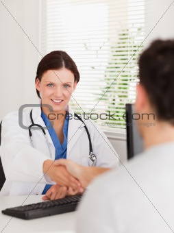 A female doctor is shaking hands with patient