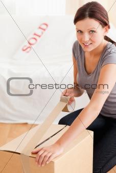 A female preparing a cardboard for transport
