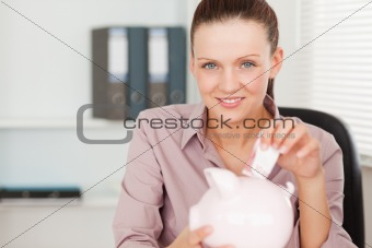 A female inserting money in piggy bank