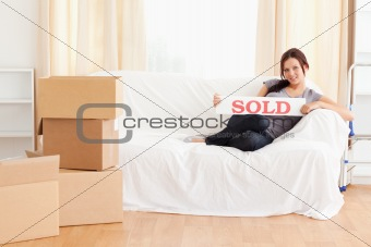 Cute woman holding a sold sign
