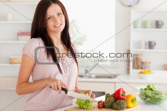 Cute woman cutting vegetables