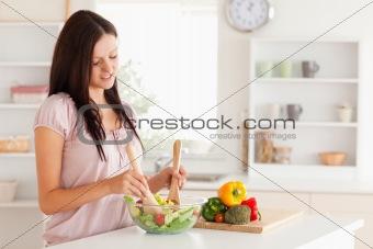 Cute woman mixing a salad
