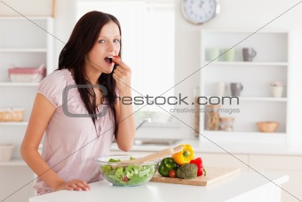 Cute woman eating vegetables