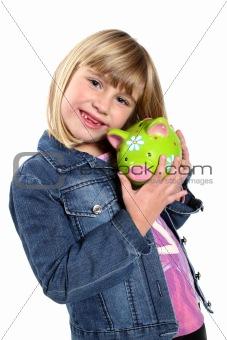 Little girl holding a green piggy bank