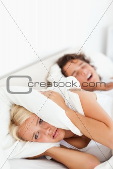 Portrait of a woman awaken by her husband's snoring