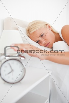 Portrait of an unhappy woman awaken by an alarmclock