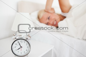 Angry woman awaken by her alarnclock