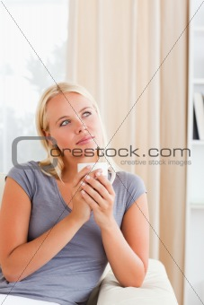 Portrait of a woman sitting on a sofa with a cup of coffee