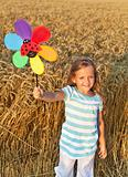 Little girl in whet field at harvest time