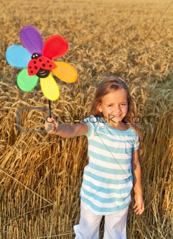 Little girl in whet field at harvest time