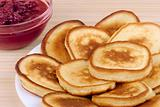 heap of pancakes with bowl of strawberry jam