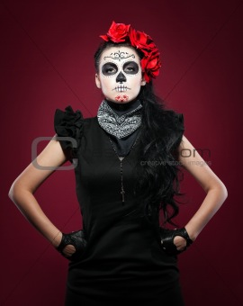Young girl in day of the dead mask on red