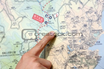 Close up of a hand pointing out location on the map.