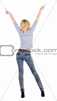 Beautiful young woman pointing at wall.