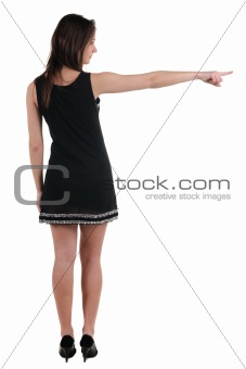 Beautiful young woman in dress pointing at wall. Rear view.