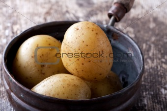 four cooked potatos in an old pan