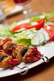 chicken meat on skewers and salad